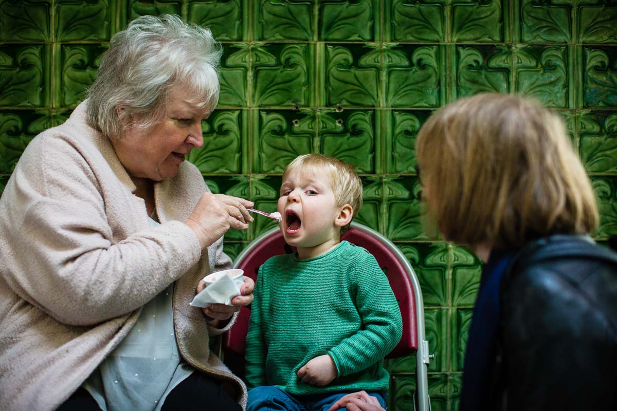 little boy with his nanna and mum, talking a bit chomp of ice cream while sat against beautiful green tiles in Victoria Baths