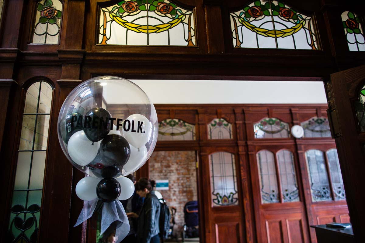 large balloon with parentfolk printed on it amongst beautiful architecture in victoria baths manchester