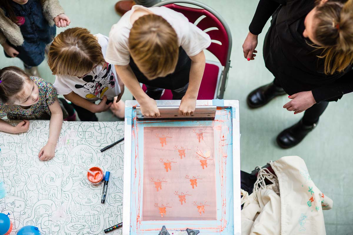 aerial shot of children screen printing bags with square pegs - fun activity for the kids