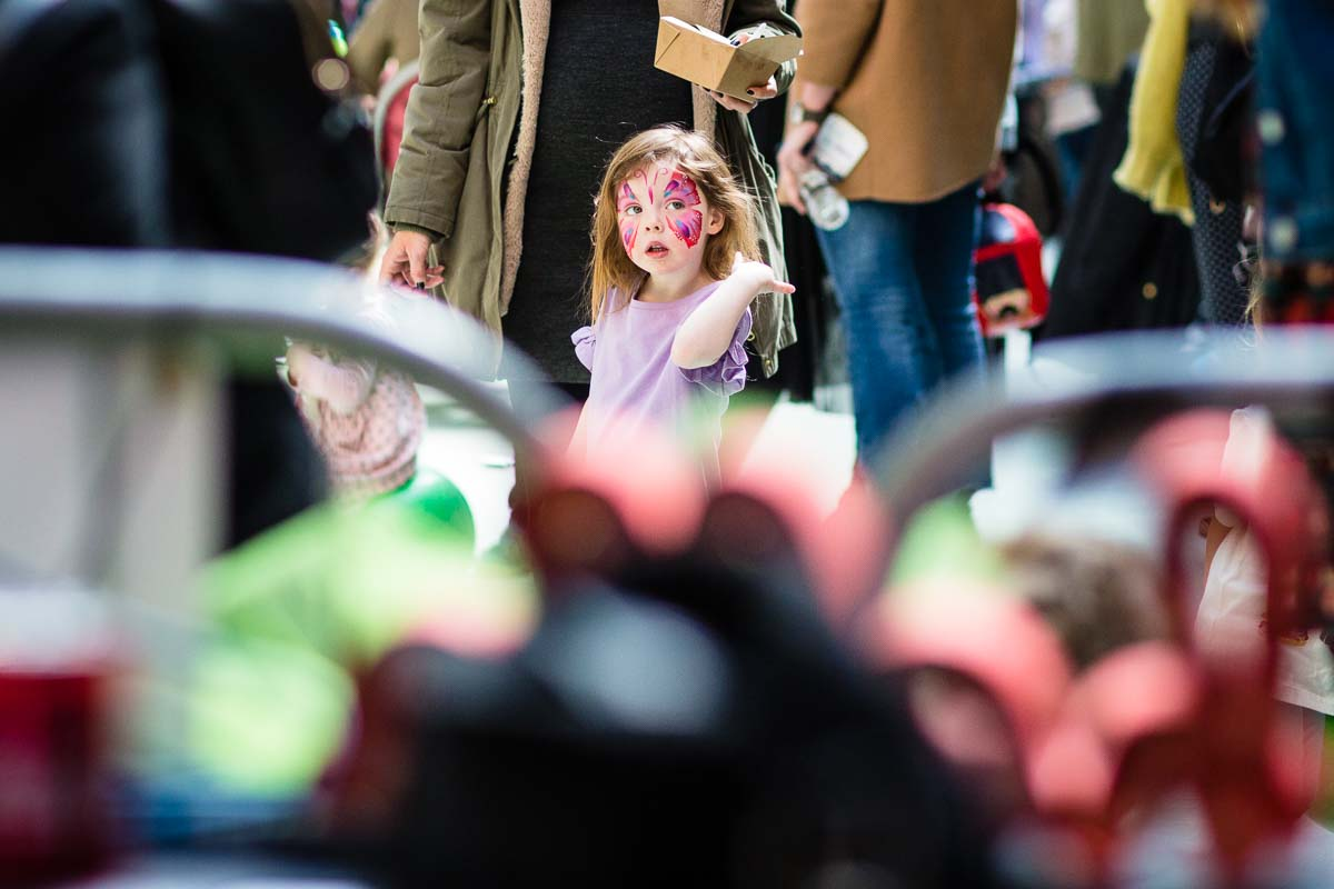 little girl looking around the venue as she is wearing a pretty butterfly face paint at family event in manchester