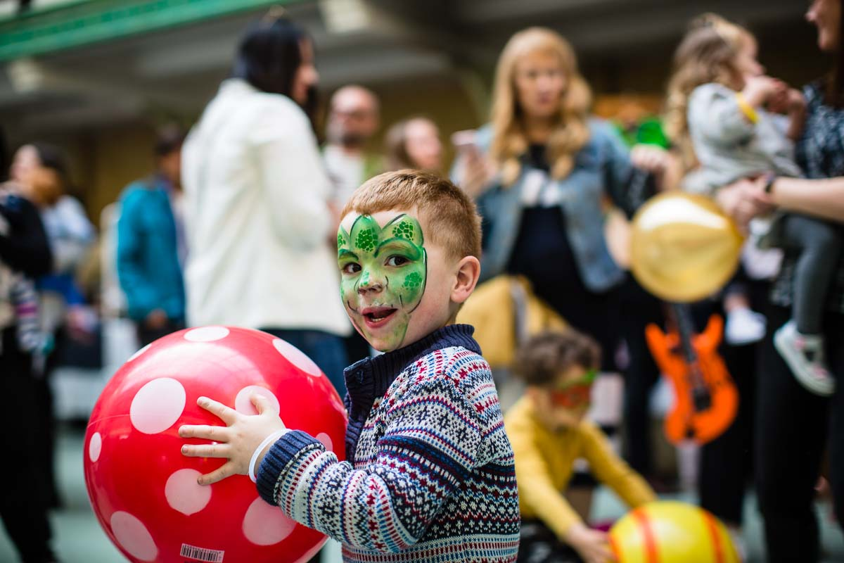 little boy with green face paint holding a red and white spotty ball