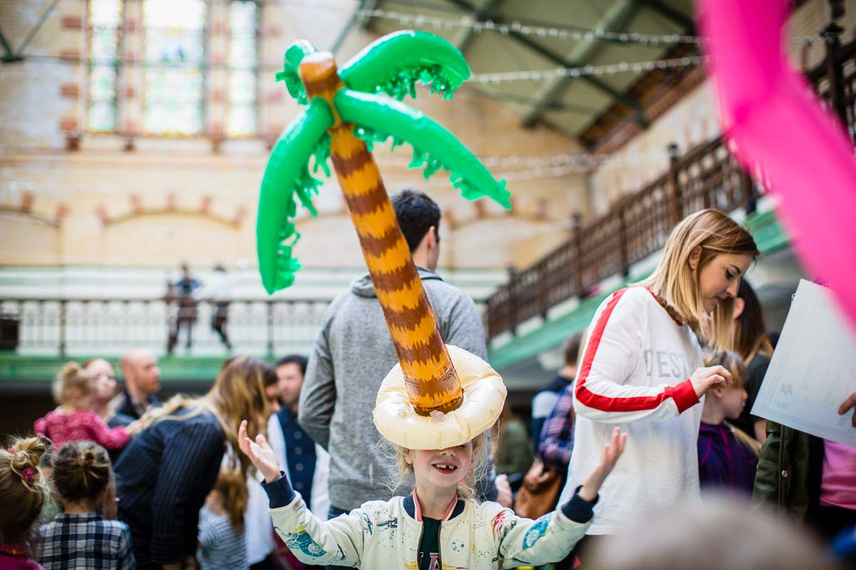 little girl balancing a palm tree inflatable on her head as she is dancing!