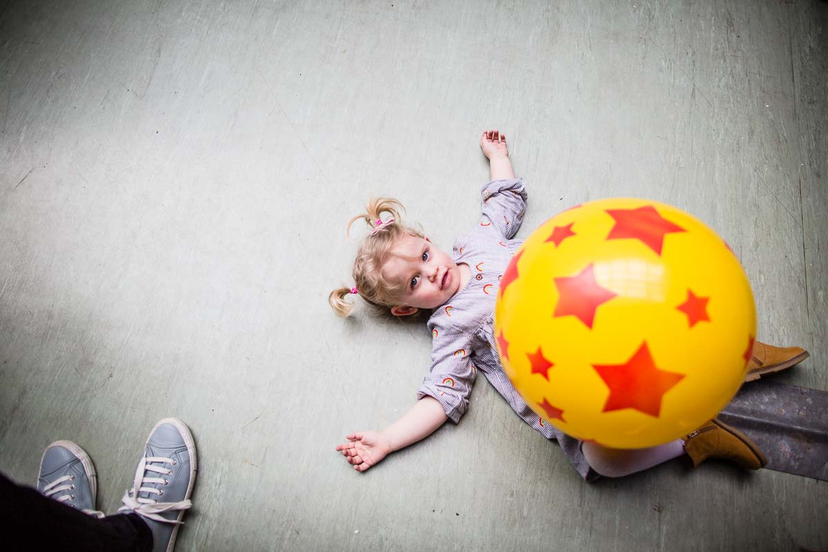 little girl lying on the dance floor with a bouncing ball resting on top of her!
