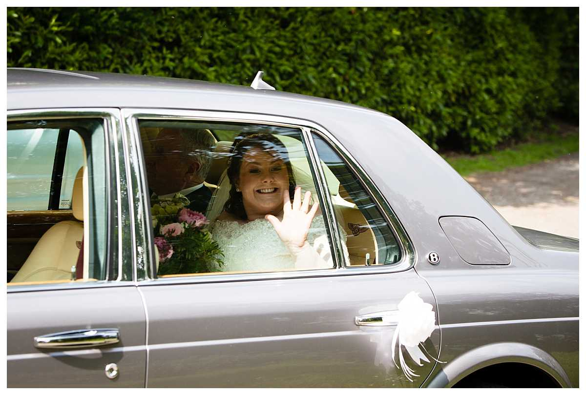 bride waving at those gathered outside church as she arrives in the wedding car, moment capture at bronington church, wales