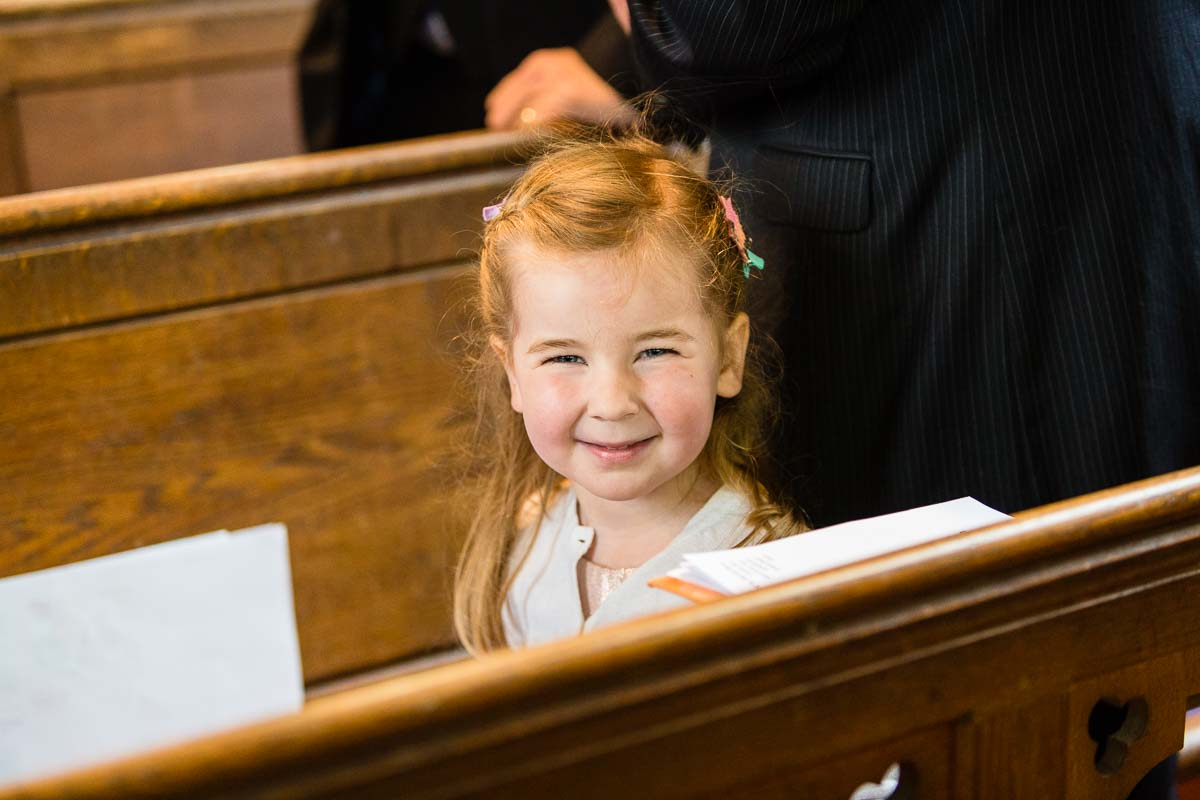 little girl smiling as she stands between church pews