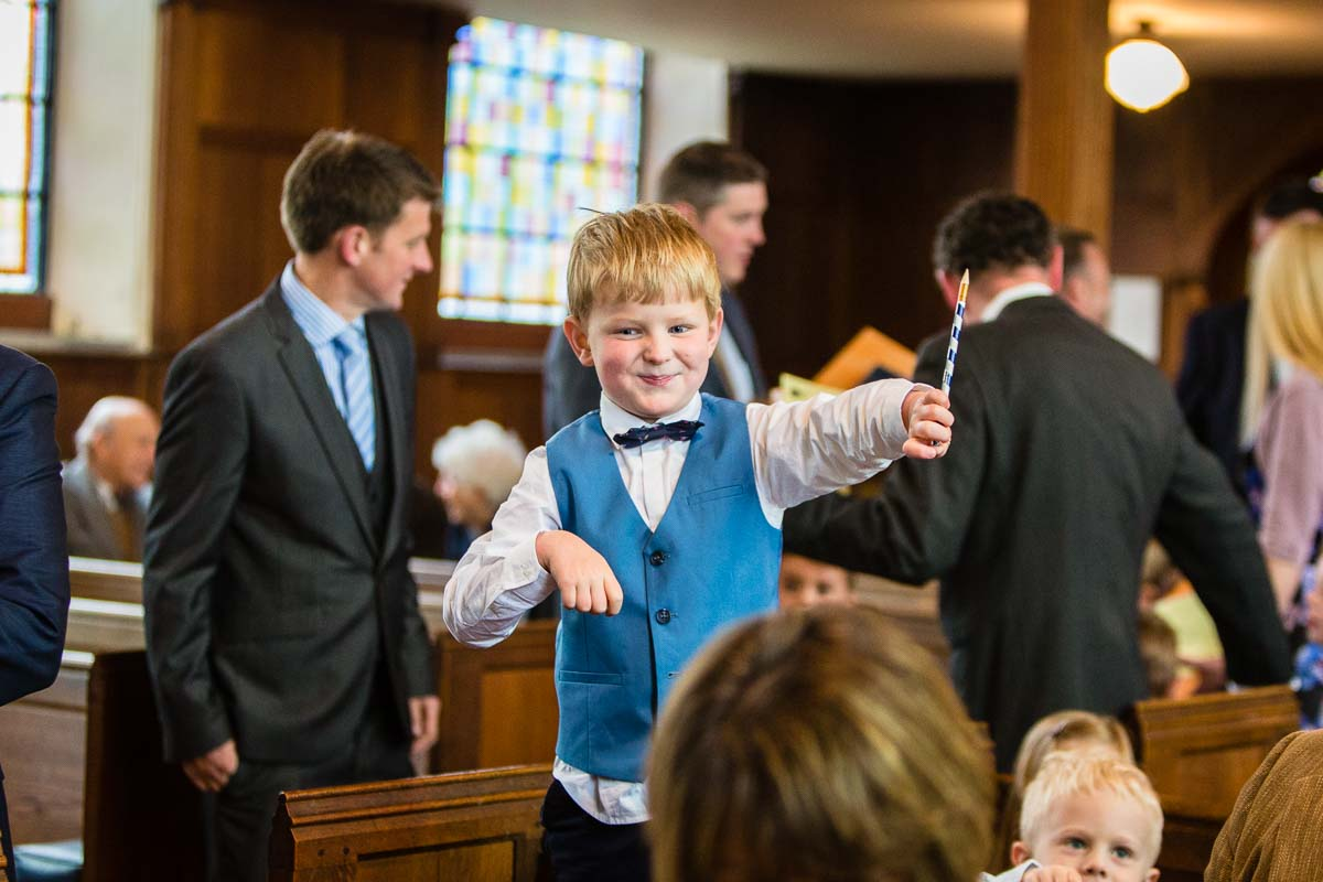 little boy play fighting before the start of the christening at Ash, Shropshire church