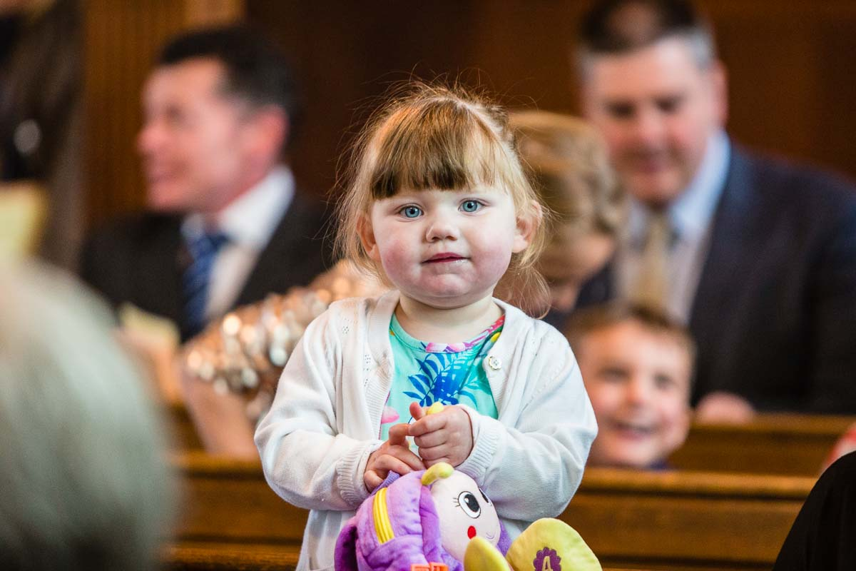 little girl with sparkling blue eyes holding her bug bag while waiting in church