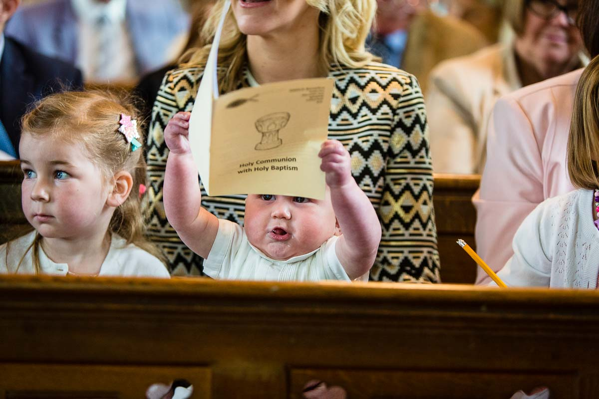 baby boy holding the order of service for christening above his head showing of beautiful brown eyes
