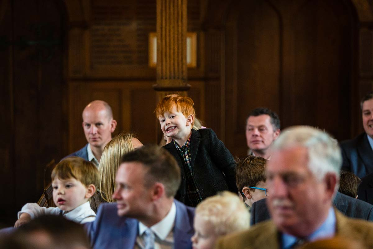 little redhead boy peeking above everyone in church with a cheeky smile