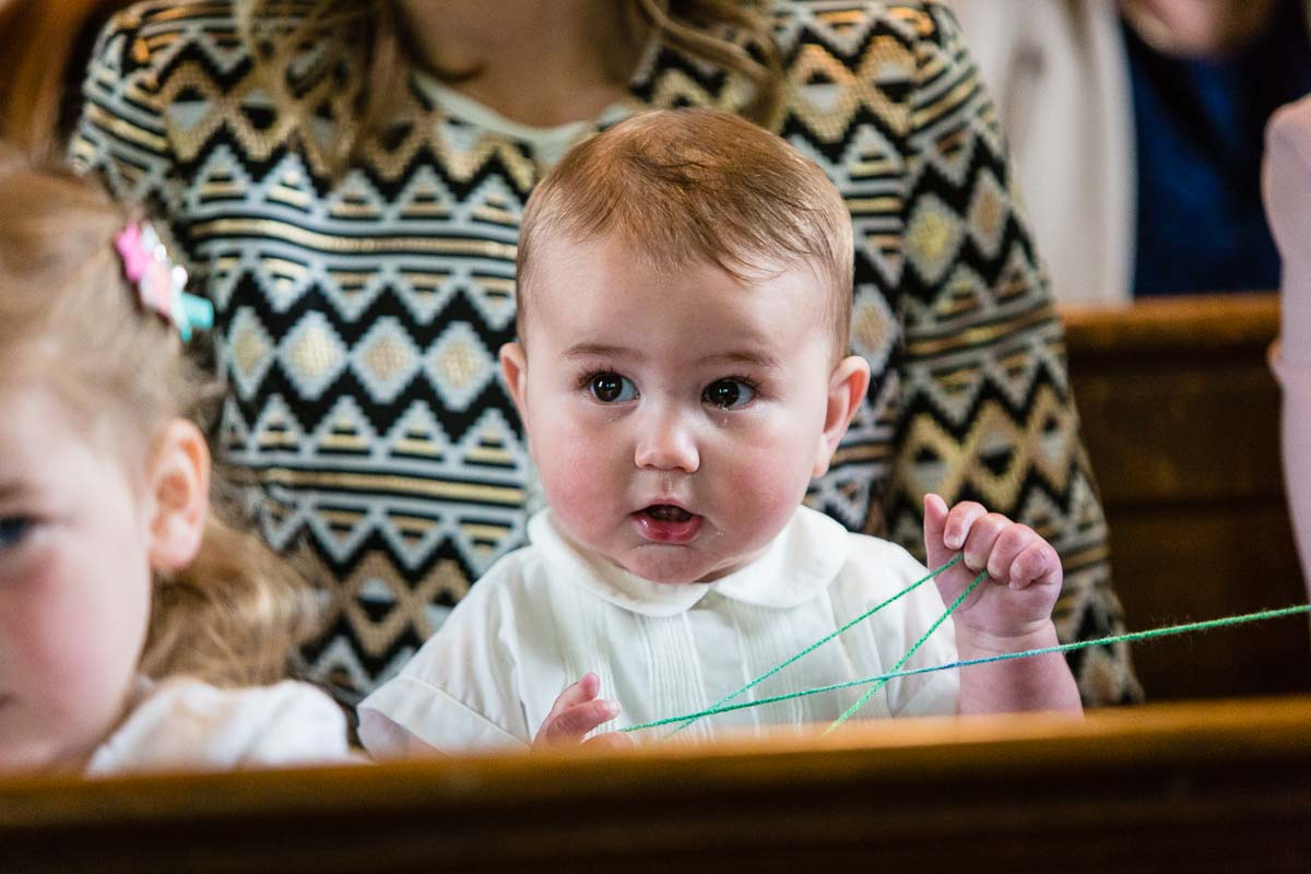 baby max with big brown eyes looking over to the vicar holding wool from the church demo