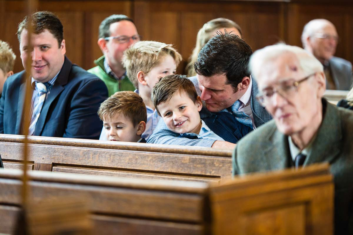 father and son playing around during christening service - candid shot by christening photographer shropshire