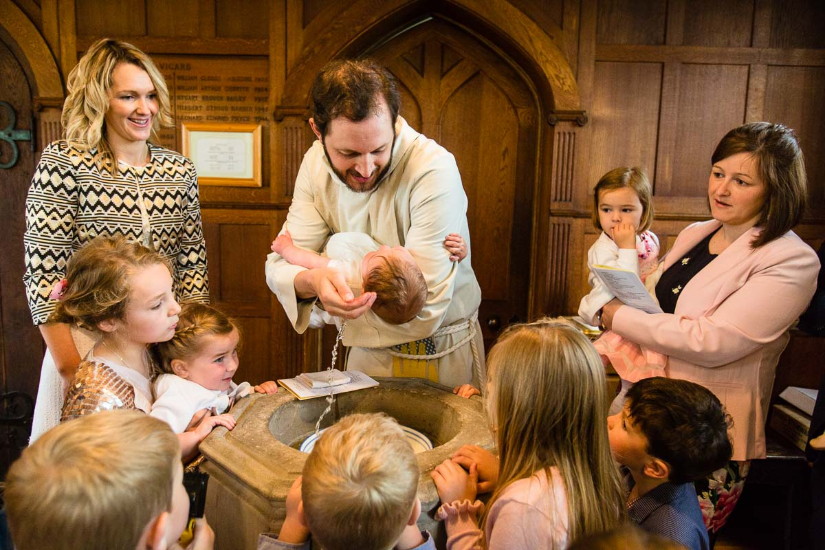 vicar pouring water over baby boy's head during baptism over the font at ash christ church shropshire