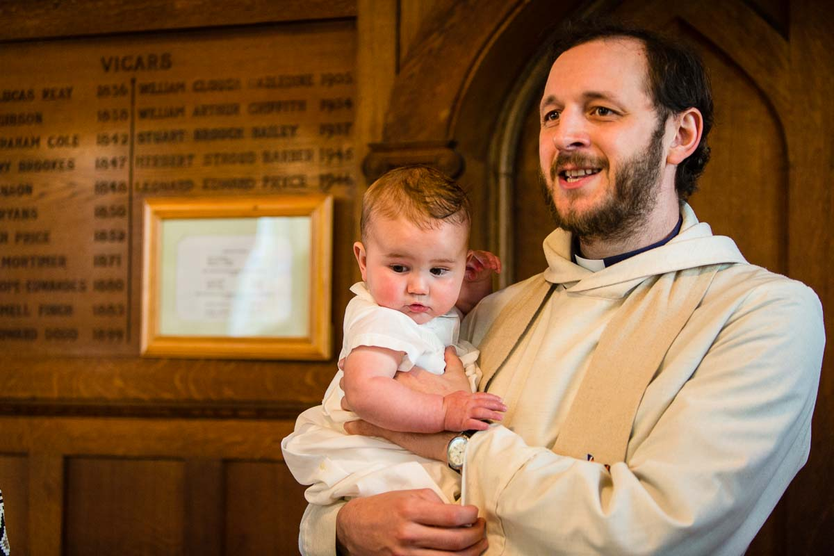 vicar holding baptised boy as he talks to the congregation