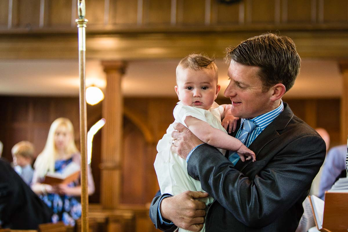 father of baby boy who was being christened nuzzling in with him as ash church christening photographer shropshire