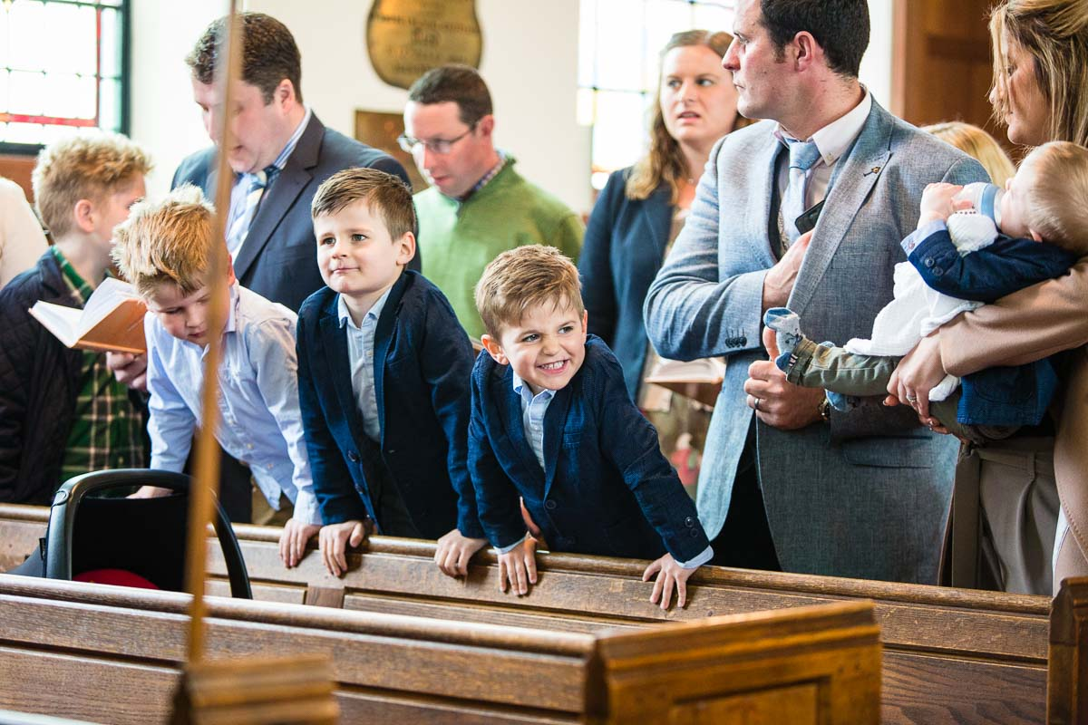 three little boys leaning on church pews being cheeky