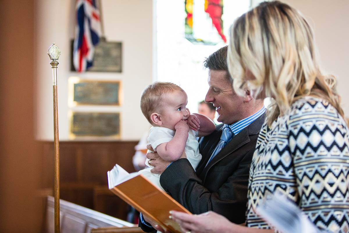 baby boy at christening giving dad eye contact