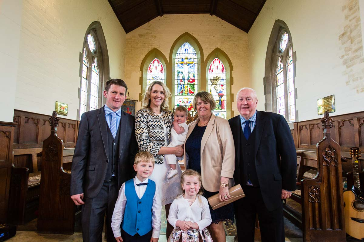 family with mum and dad - portrait in church for baby christening