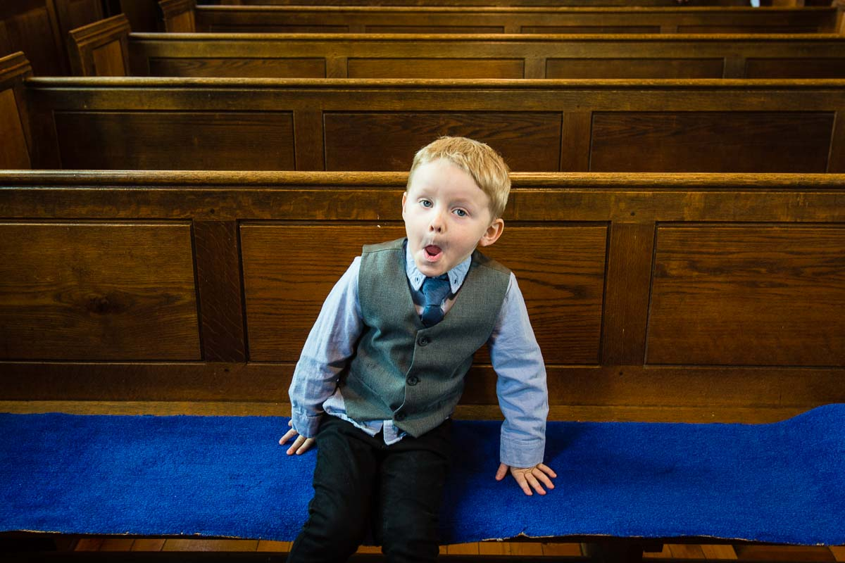 cousin pulling a funny face as he sits on a pew on his own