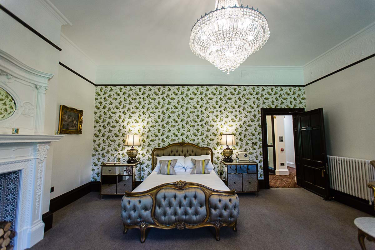 different angle of the bridal suite with beautiful large bed and vintage sage wallpaper
