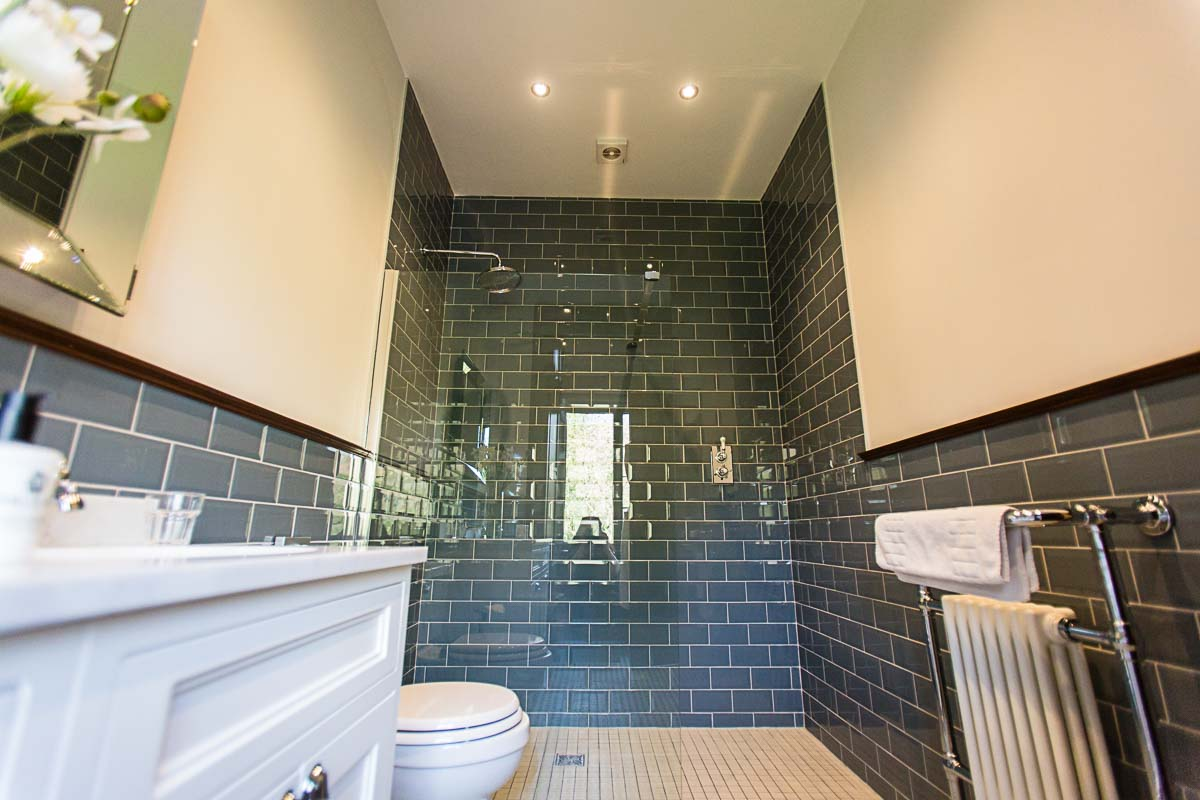 wonderful grey/blue brick style bathroom light and airy with glass panel