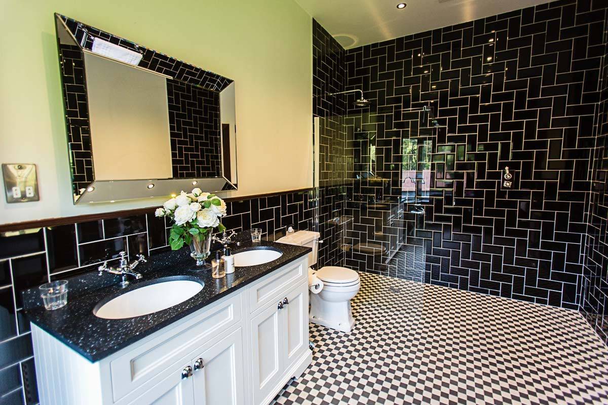 black themed bathroom with brick style tiles at tyn dwr wedding venue