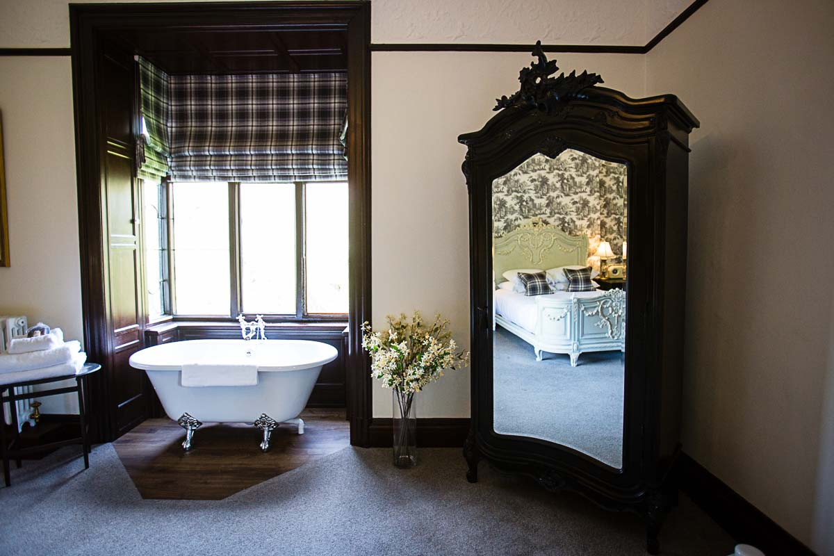 beautiful roll top bath in black themed room at tyn dwr hall