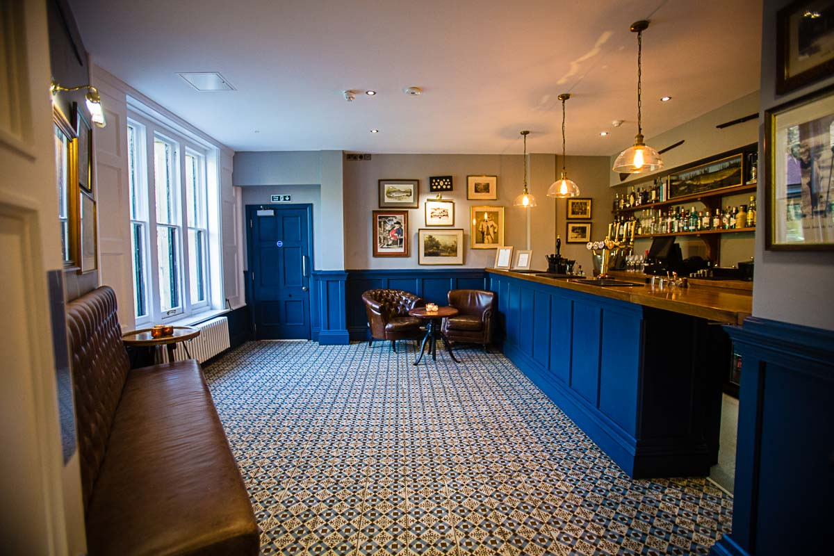 vintage blue bar, with vintage inspired tiles and tan leather seats, vintage artwork on the walls