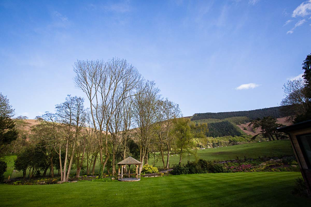 beautiful view of the gardens and the valley at tyn dwr with amazing blue sky backdrop