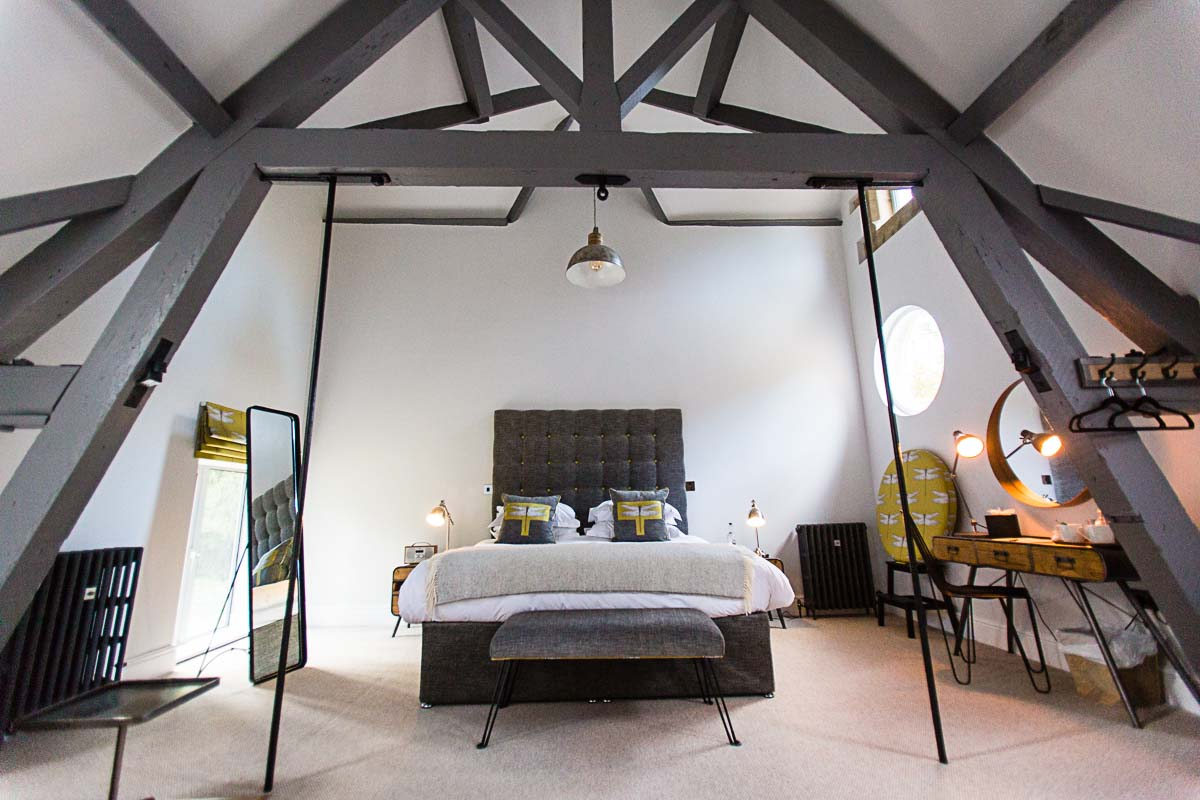 grey themed bedroom suite with amazing timber beams in tyn dwr hall accommodation