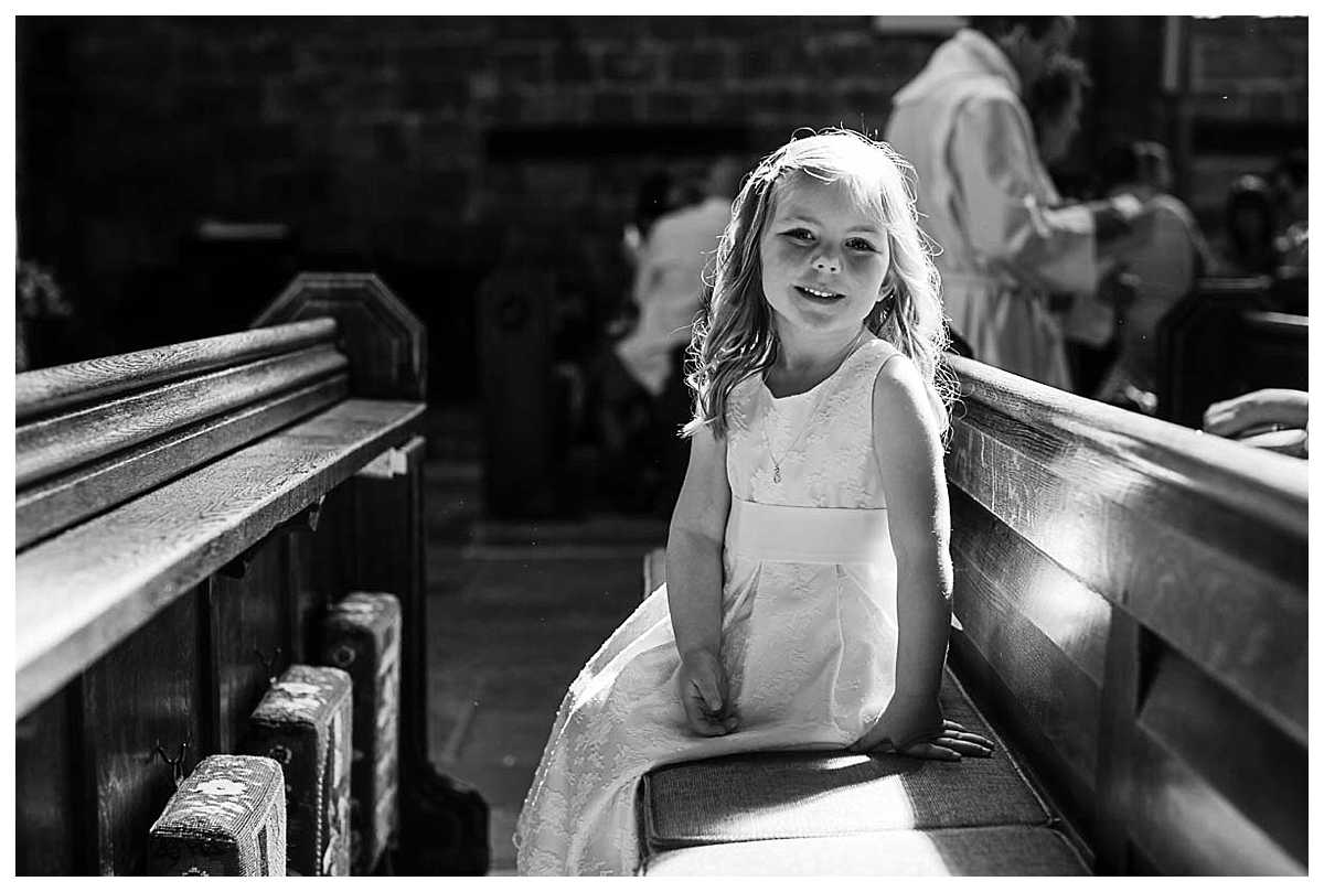 little girl who is getting christened looking happy in St. Mary's Church, Nantwich