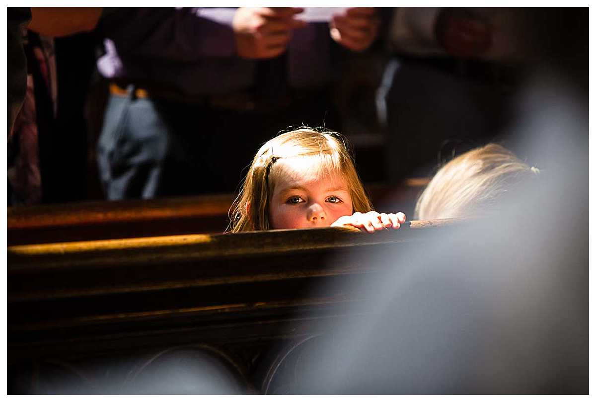little Mae peeking over the church pew in st. mary's church, nantwich