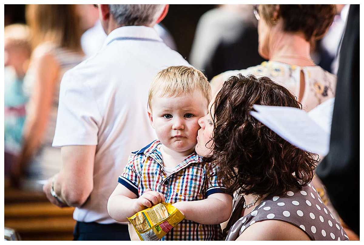 mother kissing her little boy on the cheek in church at a friends christening - St. Mary's Church, Nantwich