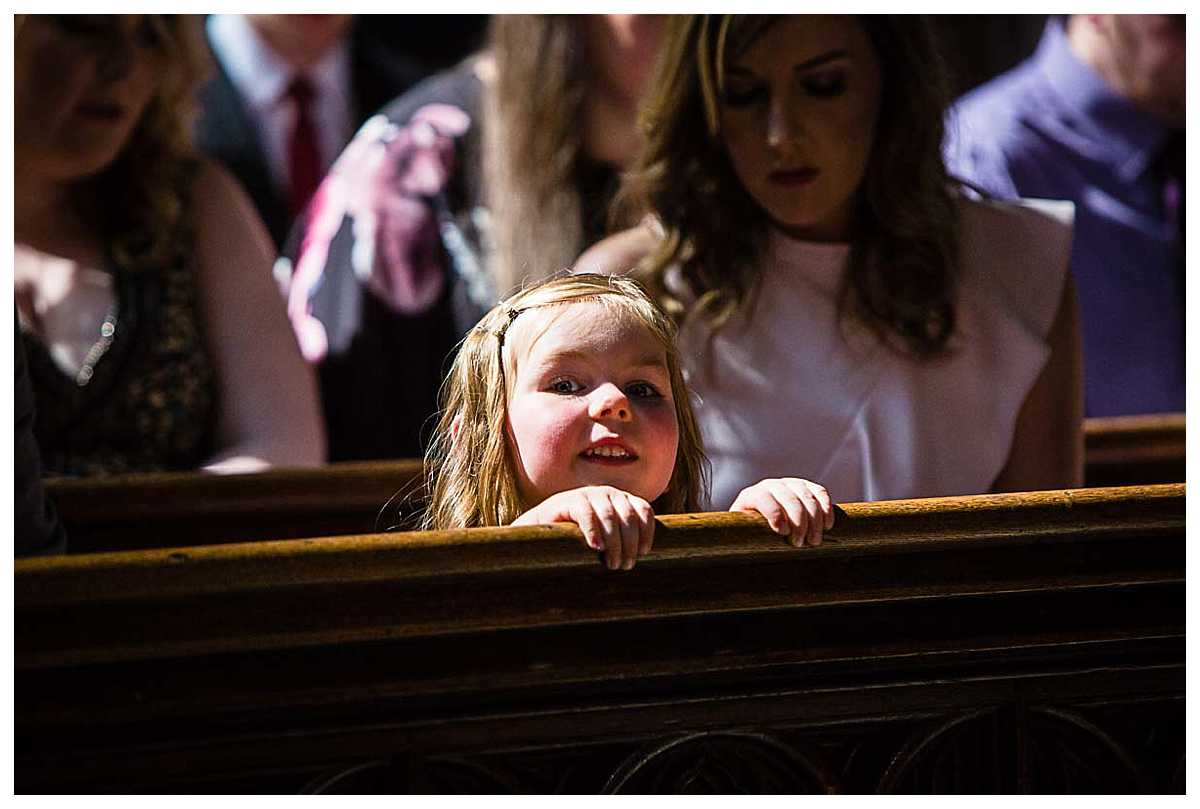 little girl peeking over the pew in church at her christening