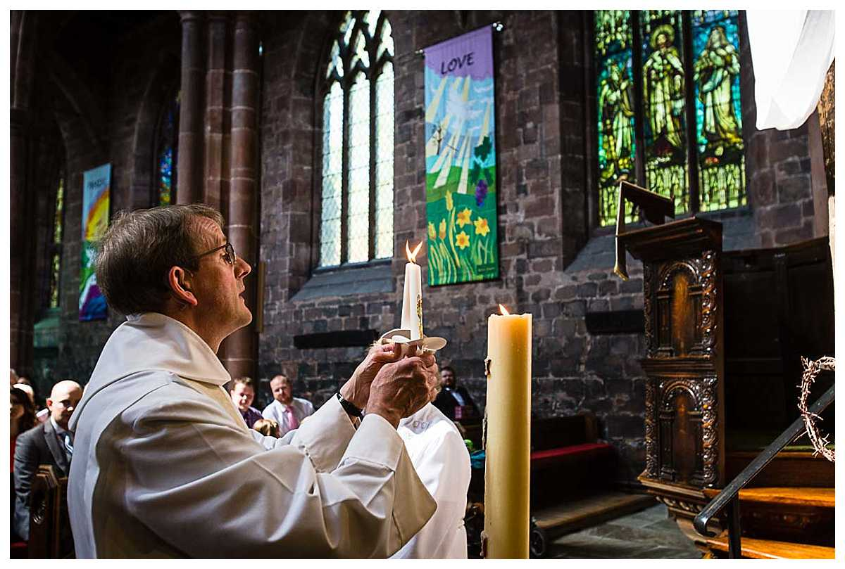 vicar lighting the christening candle from the easter candle in church during service