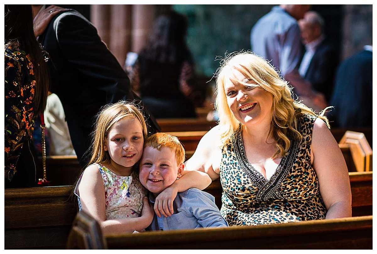 close friends of the child being christened sitting on the church pews smiling and looking happy