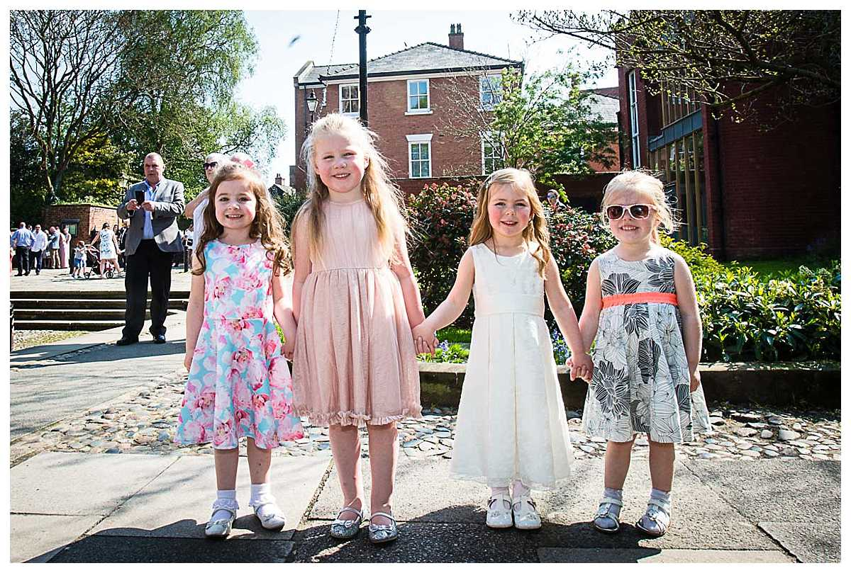 little girls holding hands outside the church after the christening