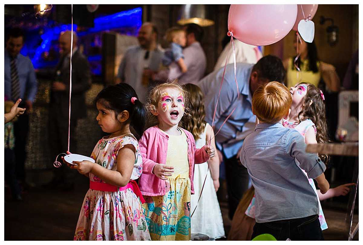 excited child as she plays with balloons at party
