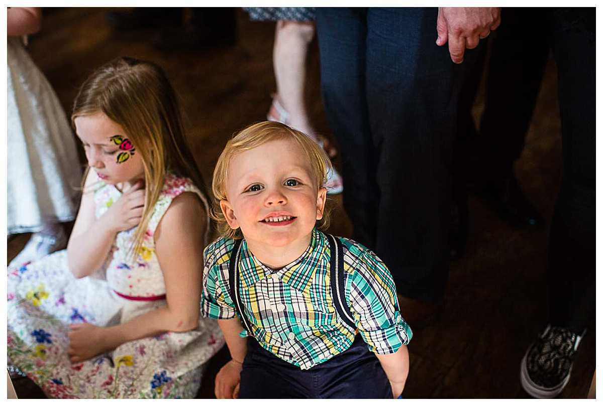 little boy with a gorgeous smile at the camera at christening party
