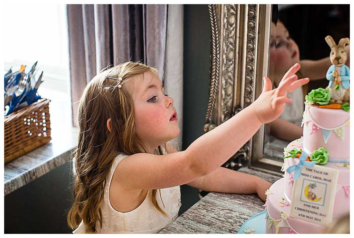 little girl sneaking around christening cake and reach up to touch it