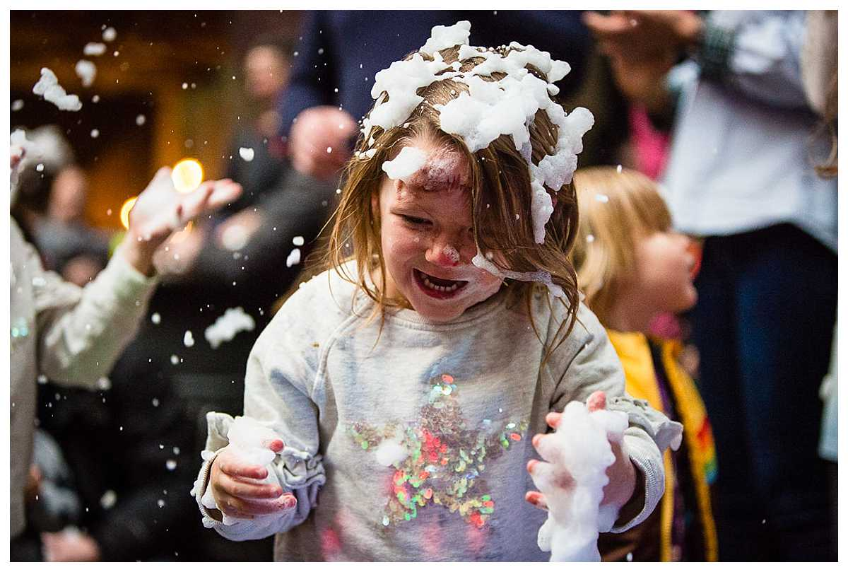 little girl covered in fake snow and looking so excited to be playing