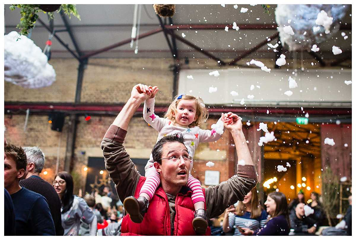 little girl sat on her dad's shoulders watching the bubbles and fake snow coming out of the machine