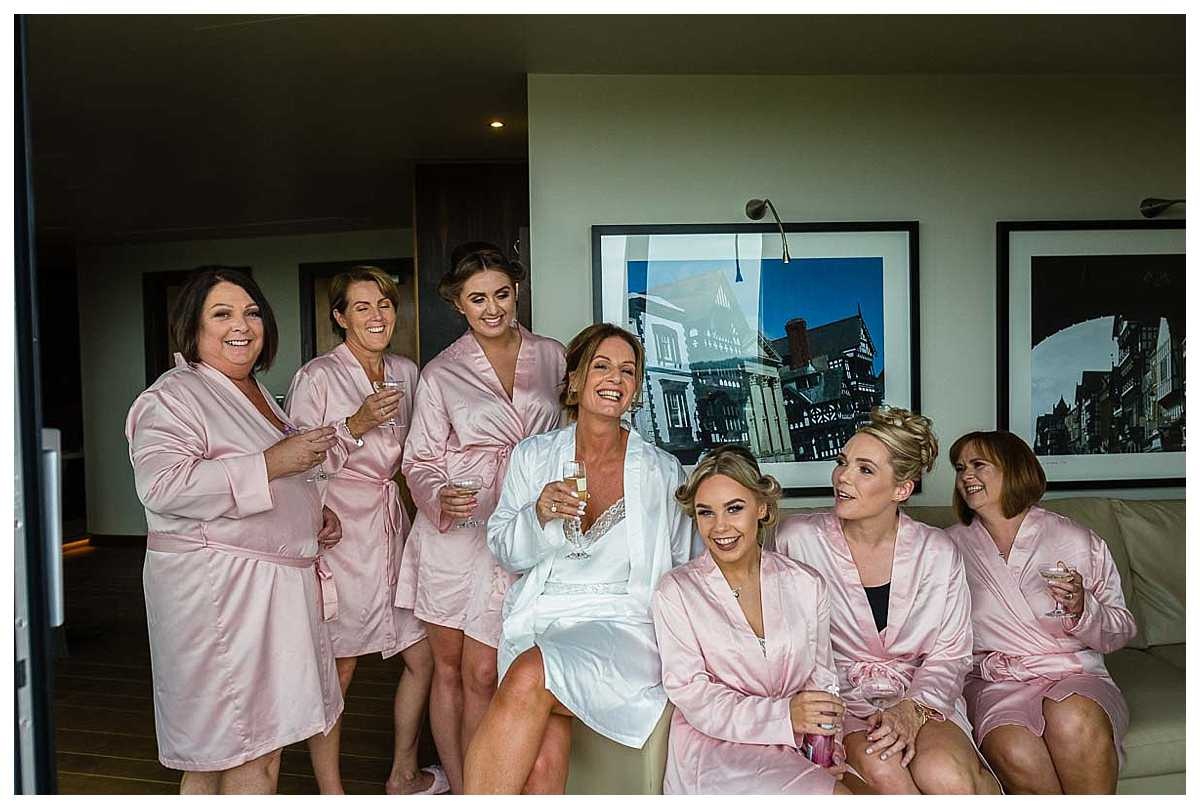 bride sitting with her girl friends laughing as she gets ready for her wedding at chester racecourse
