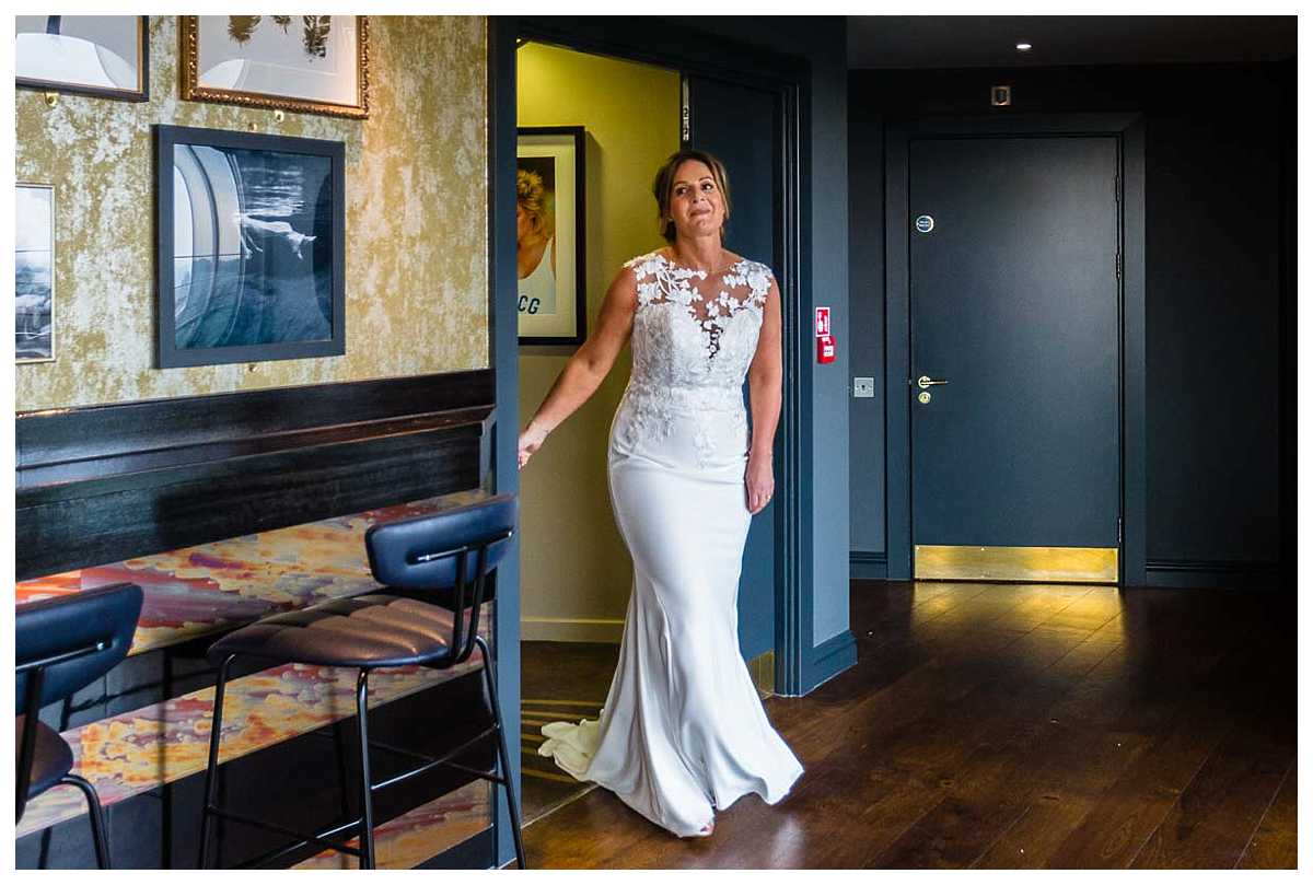 bride walking into the bar at the abode chester, to see her husband in her new dress