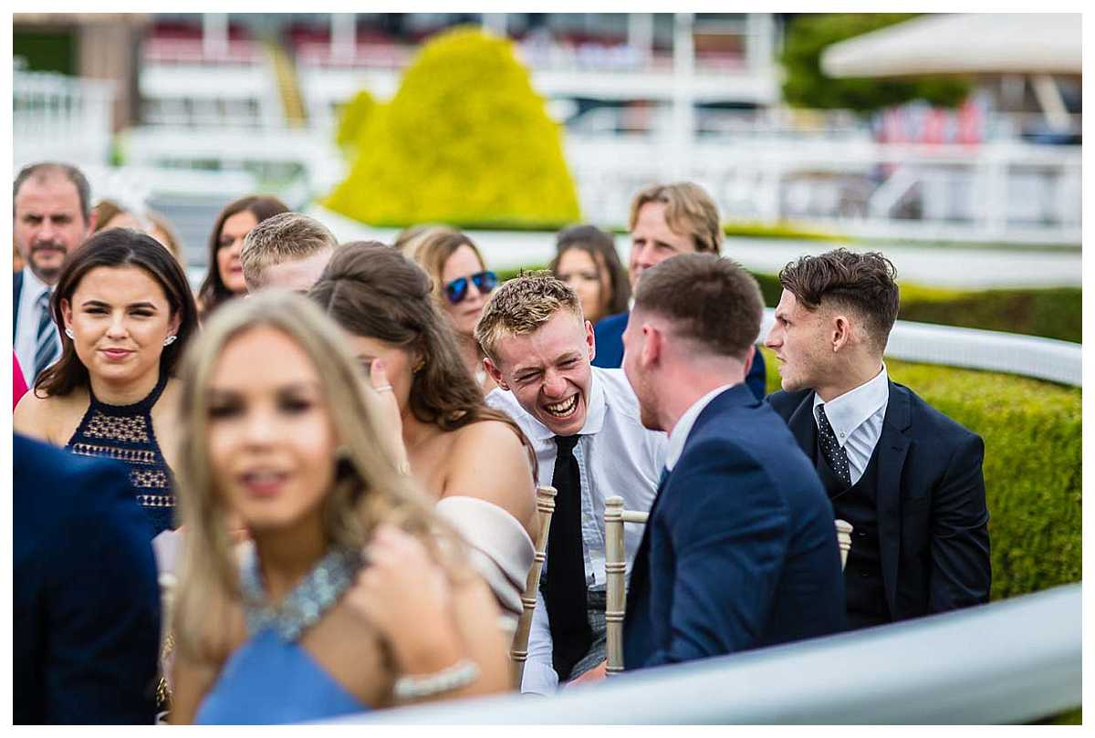 guest sitting in the parade ring laughing out loud while waiting for the bride and groom