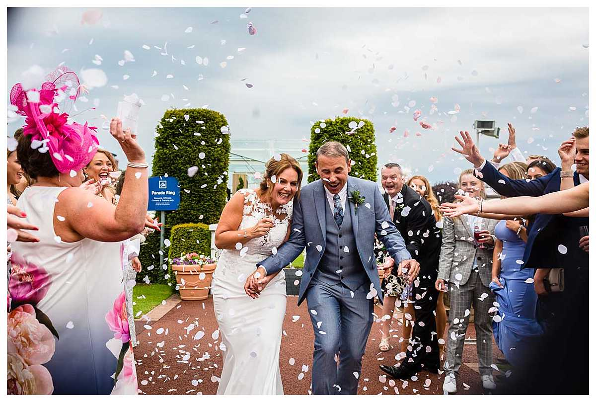 confetti being thrown at the bride and groom after their ceremony at chester racecourse