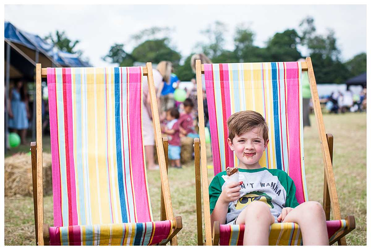 young boy sat with a yummy ice cream sat on over sized deckchairs
