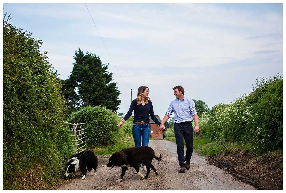 bride and groom to be walking down country road with family dogs