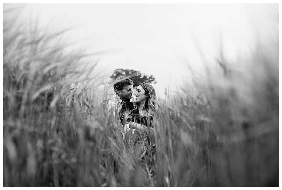 bride and groom to be looking happy as they have a moment in the wheat field on their shropshire pre-wedding shoot