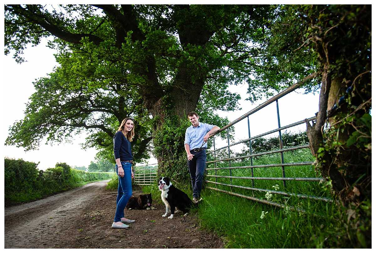 happy couple leaning against a country gate with their well trained dogs