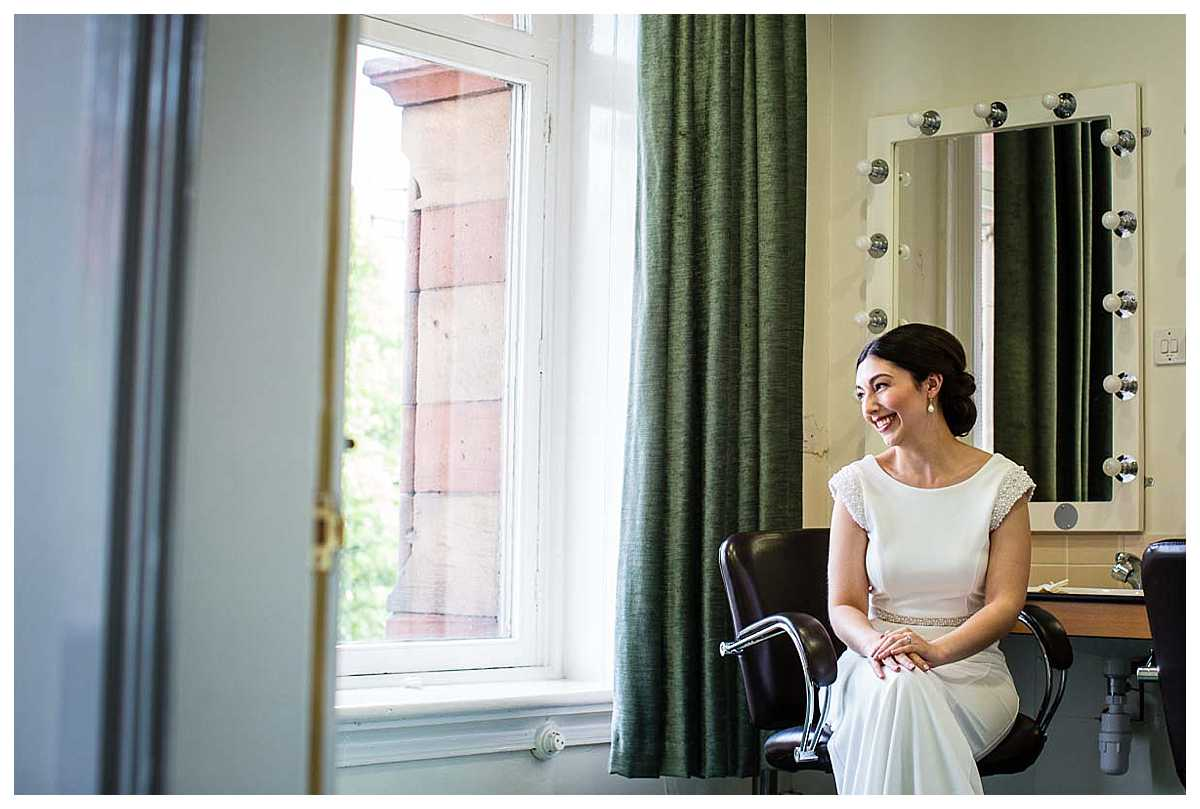 bride sat in green room of the town hall chester looking incredibly excited to get married